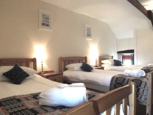 3 single beds with Melin Tregwynt cushions and antique Welsh bedspread in Ty Mortimer holiday cottage St Davids Pembrokeshire