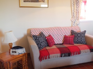 Melin Tregwynt cushions on comfortable sofa with ceramic vase Ty Mortimer holiday cottage